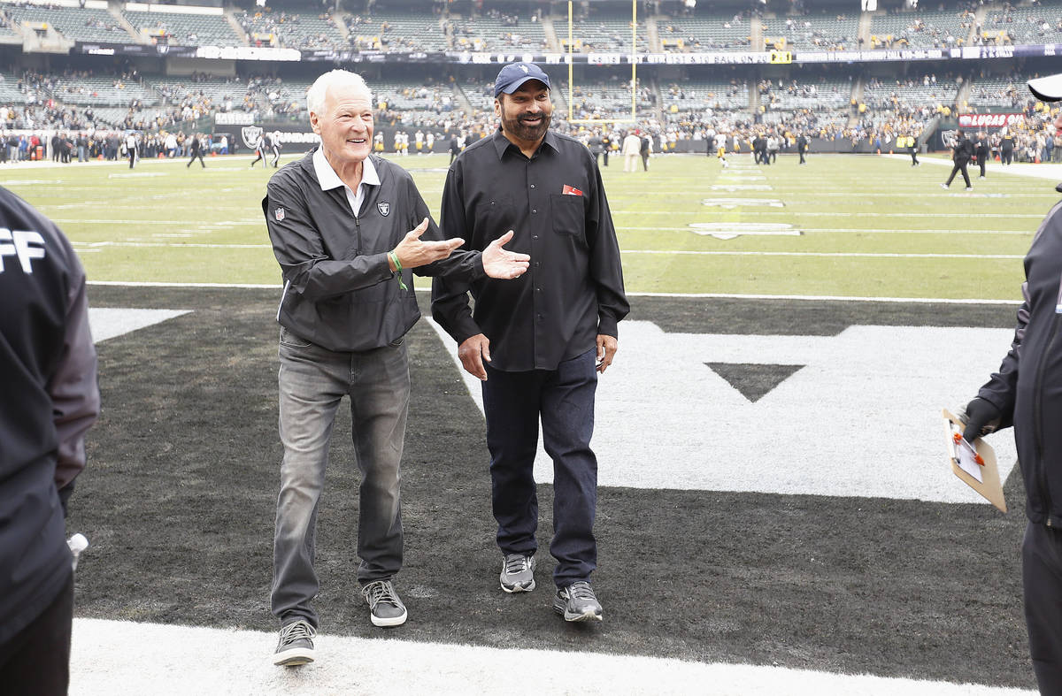 Former Oakland Raiders linebacker Phil Villapiano, left, walks with former Pittsburgh Steelers ...