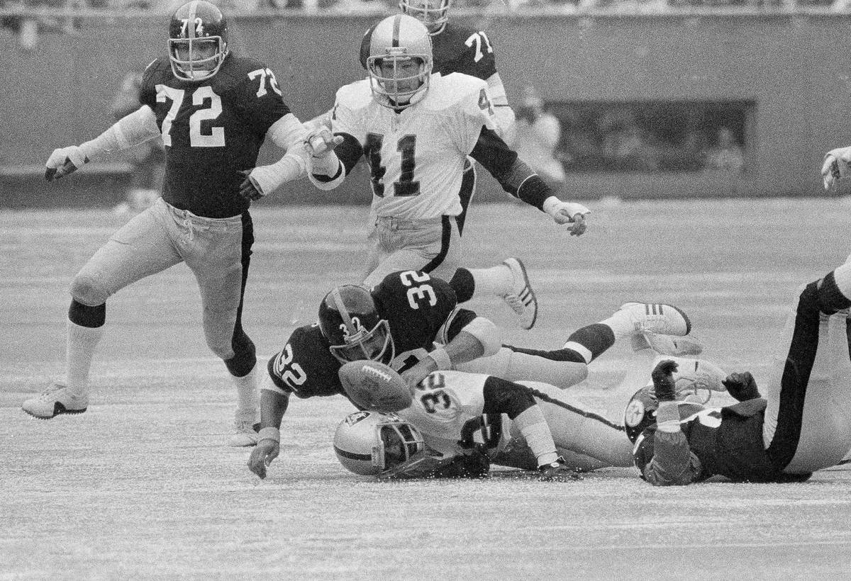 Raiders Jack Tatum, (32) is on the ground as he and Steelers Franco Harris (32) go after the ba ...