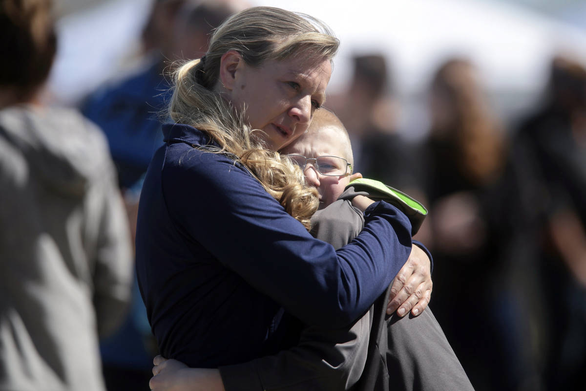 People embrace after a school shooting at Rigby Middle School in Rigby, Idaho, Thursday, May 6, ...