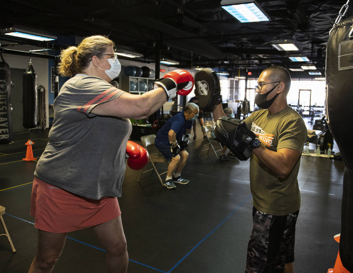 Gwen Vaughn, 48, works with Orlando Illustrismo, head coach, during her first boxing class at T ...