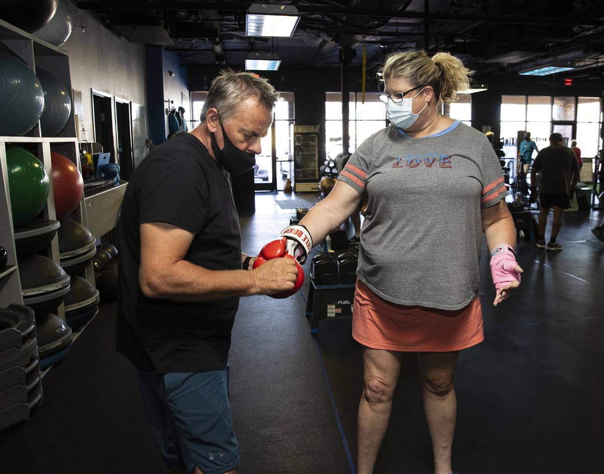 Robert Vlcek, a volunteer trainer, helps Gwen Vaughn, 48, put her boxing gloves on prior to her ...