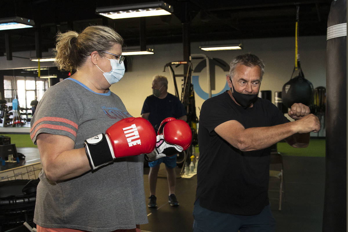 Robert Vlcek, a volunteer trainer, demonstrates to Gwen Vaughn, 48, how to punch the bag during ...