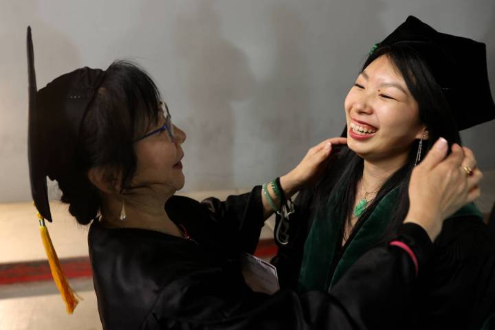 Doris Chan and her mother Mei Lun Qiu, who will do the hooding, prepare before the first gradua ...