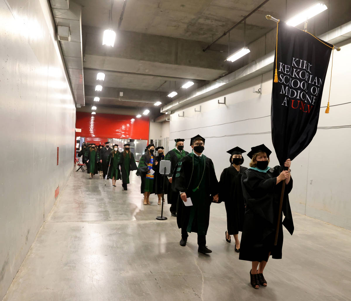 Student Marshal and Director of Student Affairs Ann Diggins leads the first graduating class of ...