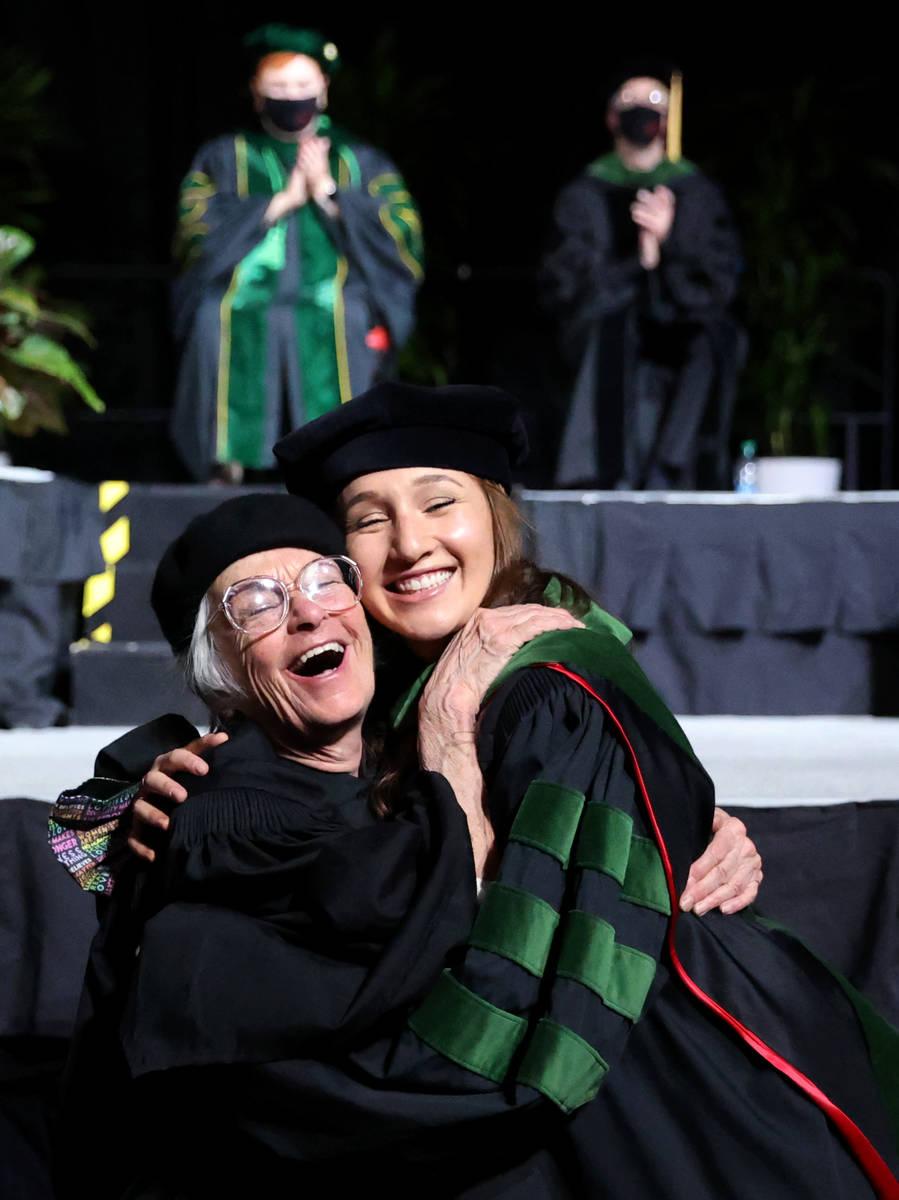 Zarah Rosen gets a hug from her grandmother Harriet Rosen after the senior Rosen hooded her gra ...