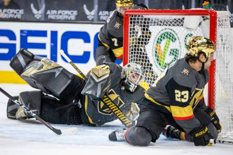 Golden Knights goaltender Robin Lehner (90) teams up to defend the net with defenseman Alec Mar ...