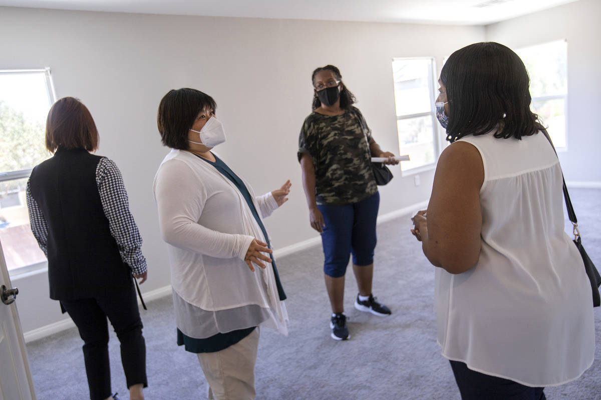 Yvonne Khoo, a realtor with eXp Realty, center left, shows a home to Coree McGinnis and Bonita ...