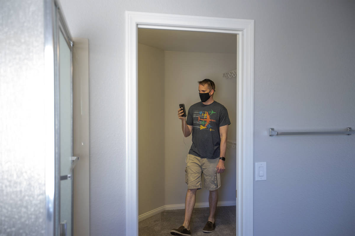 Joshua Winningham video chats with his wife during an open house at 2412 Craggy Ledge Avenue on ...