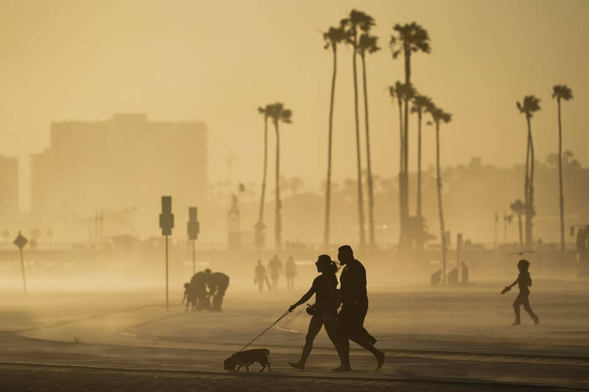 People walk on a beach path as evening winds kick up sand in Long Beach, Calif., in April 2021. ...