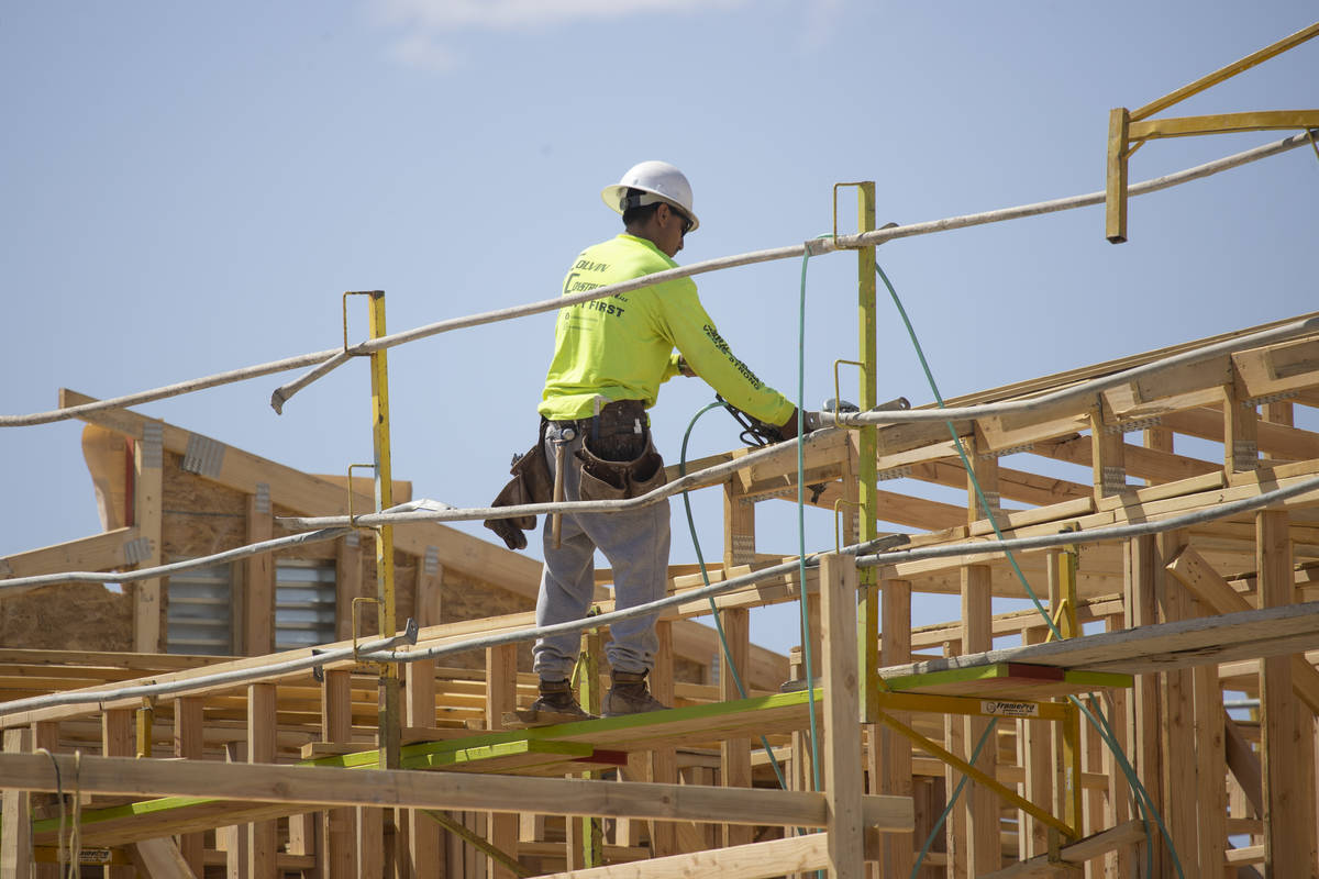 A construction worker builds the roof of a home near W Elkhorn Road and N Aviary Way in North L ...