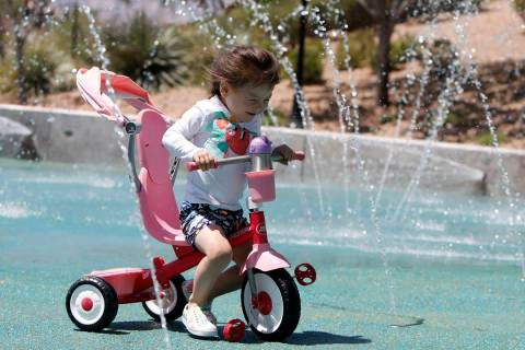 Luna Gyes, 2, of Summerlin rides a tricycle through the splash pad at Paseos Park in Las Vegas ...