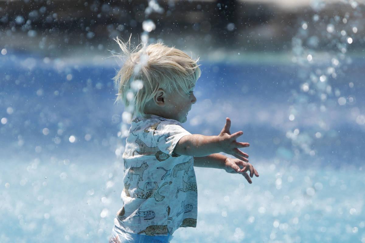 Aegis Burris, 1, of Summerlin runs through the splash pad at Paseos Park in Las Vegas, Saturda ...