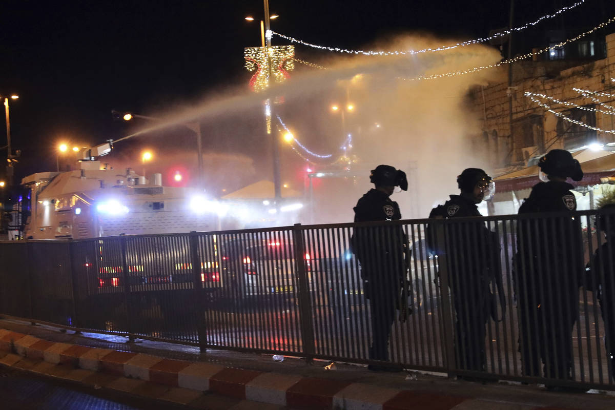 Israeli police use a water cannon to disperse Palestinian protesters from the area near the Dam ...