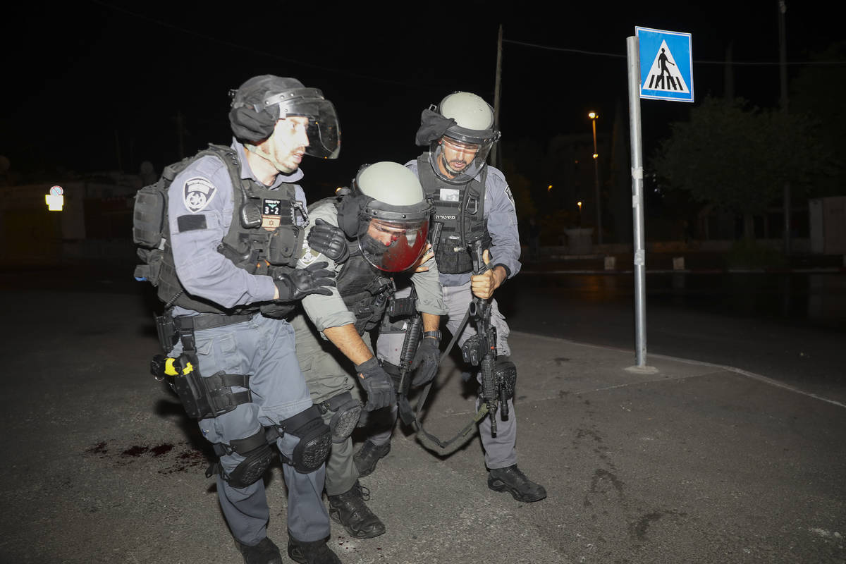An injured Israeli police officer is helped during clashes with Palestinian protesters, in east ...