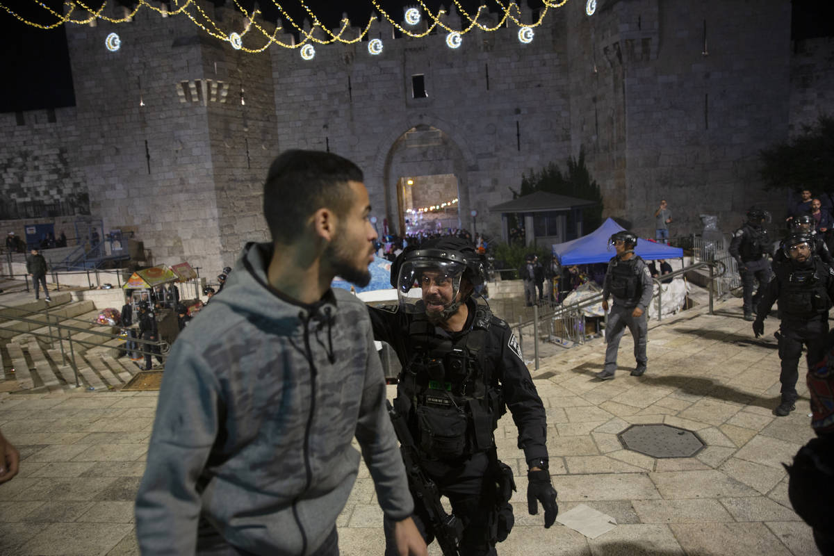 An Israeli policeman shouts at a Palestinian man to leave the Damascus Gate to the Old City of ...