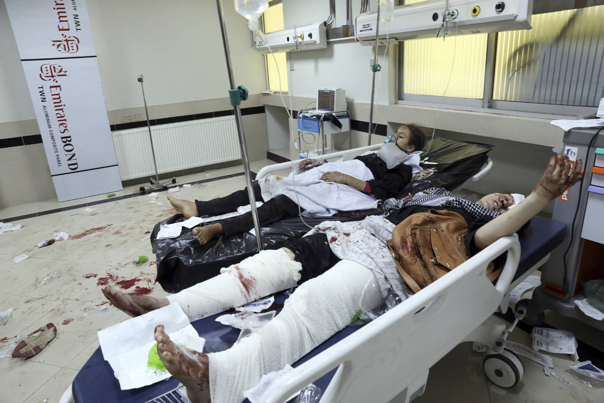 Afghan school students treated at a hospital after a bomb explosion near a school in west of Ka ...
