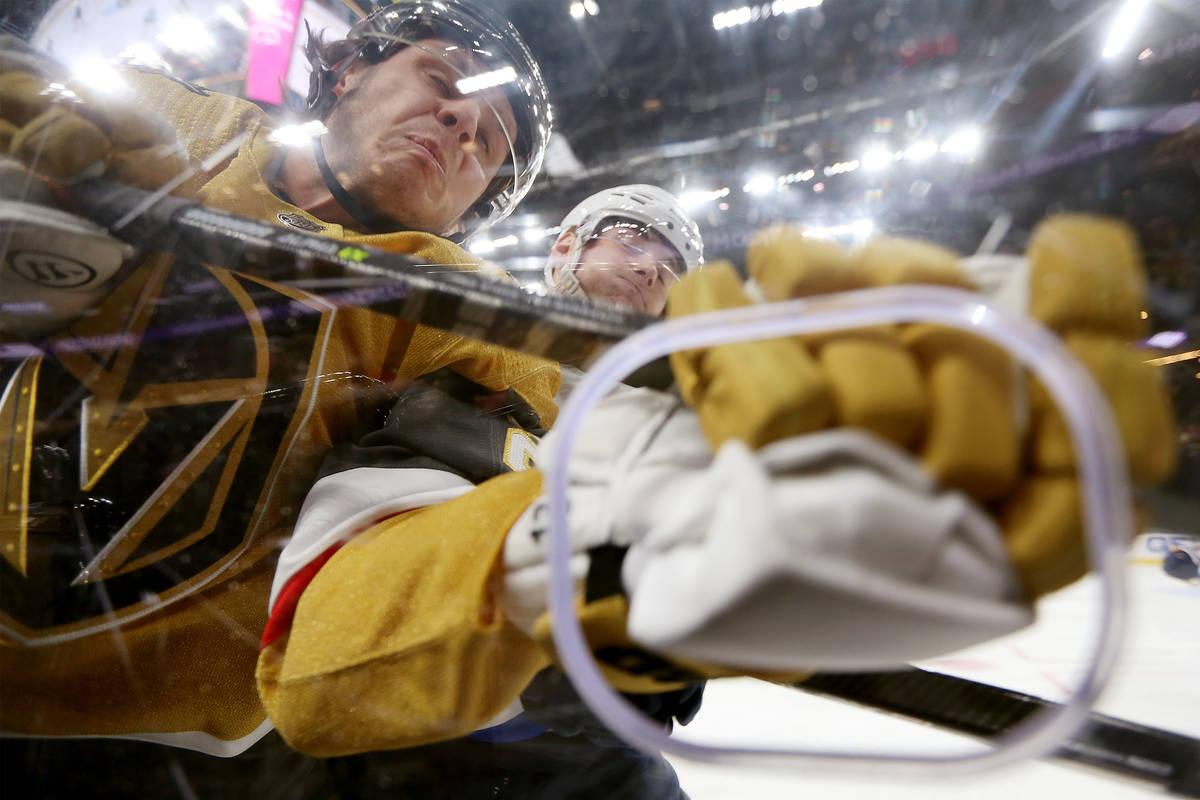 Vegas Golden Knights center Mattias Janmark (26) is slammed against the glass by St. Louis Blue ...