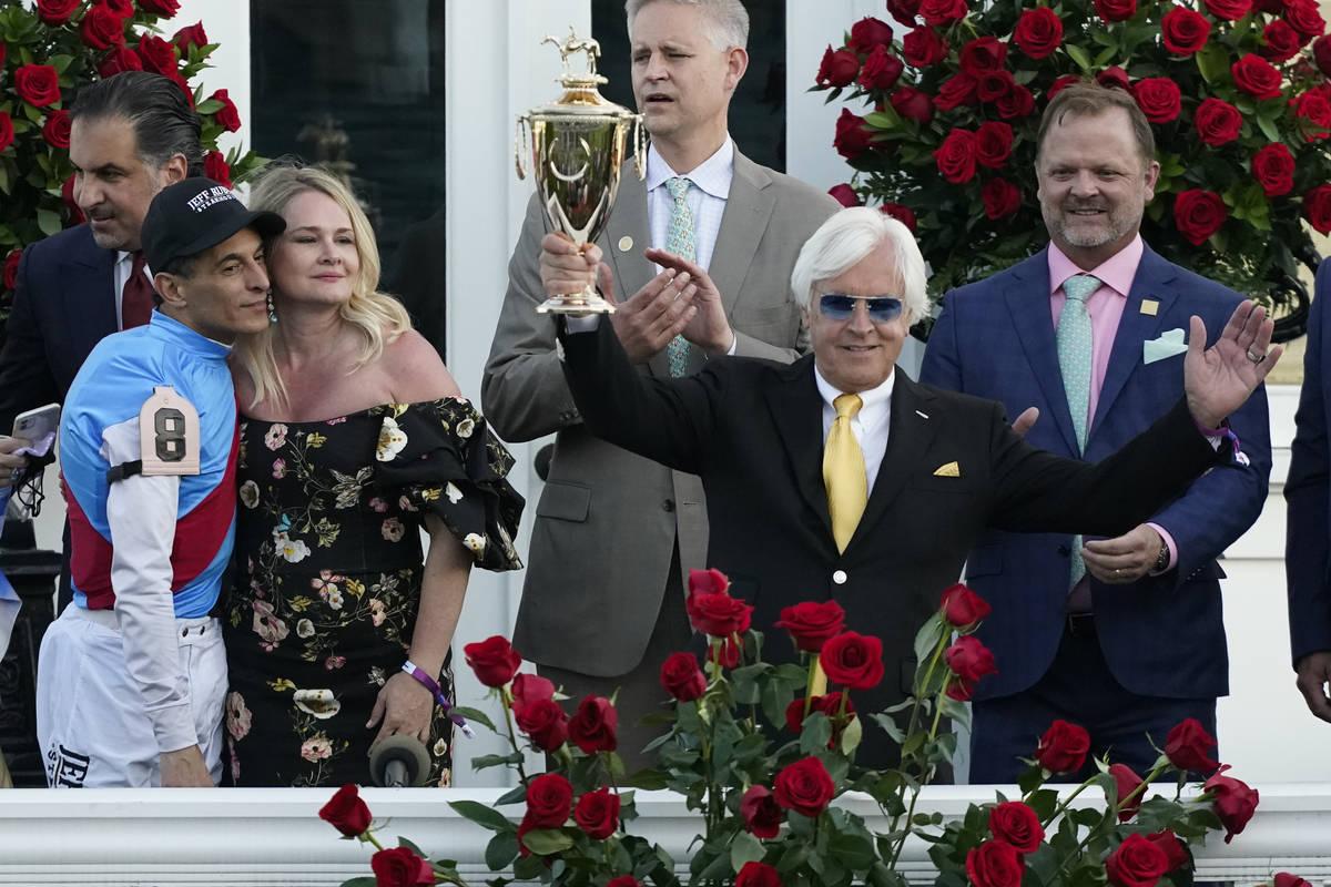 Jockey John Velazquez, left, watches as trainer Bob Baffert holds up the winner's trophy after ...