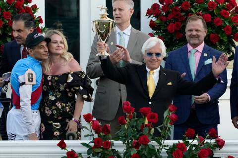 Jockey John Velazquez, left, watches as trainer Bob Baffert holds up the winner's trophy after ...