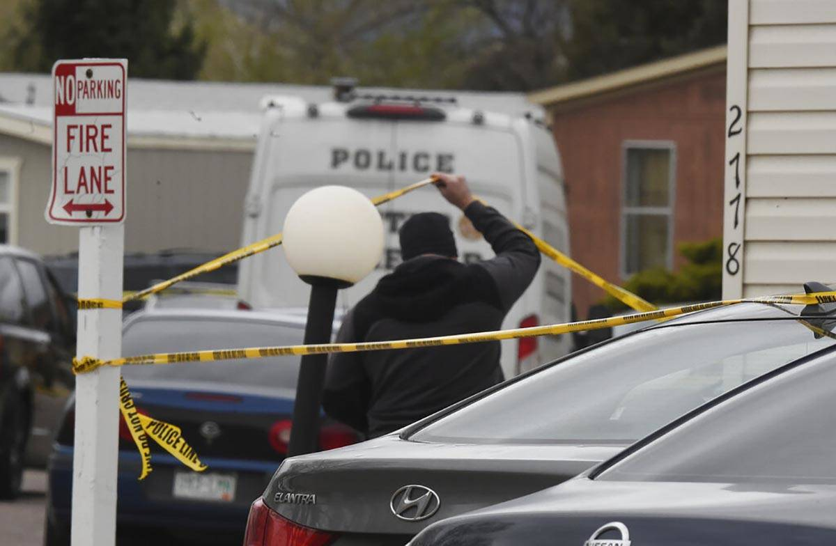 A Colorado Springs Police Department officer lifts up crime tape at the scene where multiple pe ...