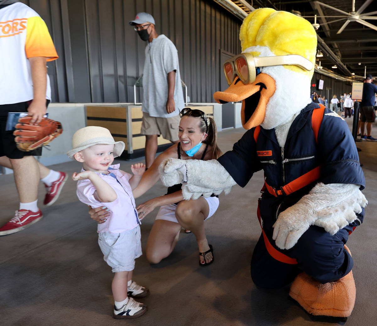 Janel Hansen and her son Ryker greet Spruce the mascot on the concourse at Las Vegas Ballpark a ...