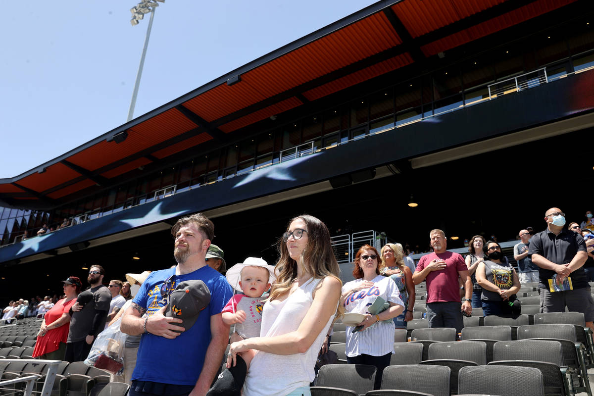Kelsey Law stands for the National Anthem with her son Chandler, 11 months, and husband Matt at ...