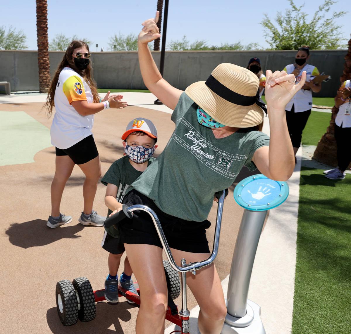 Rena Van Slyke and her son Dodge, 4, celebrate winning the tricycle race between innings as the ...
