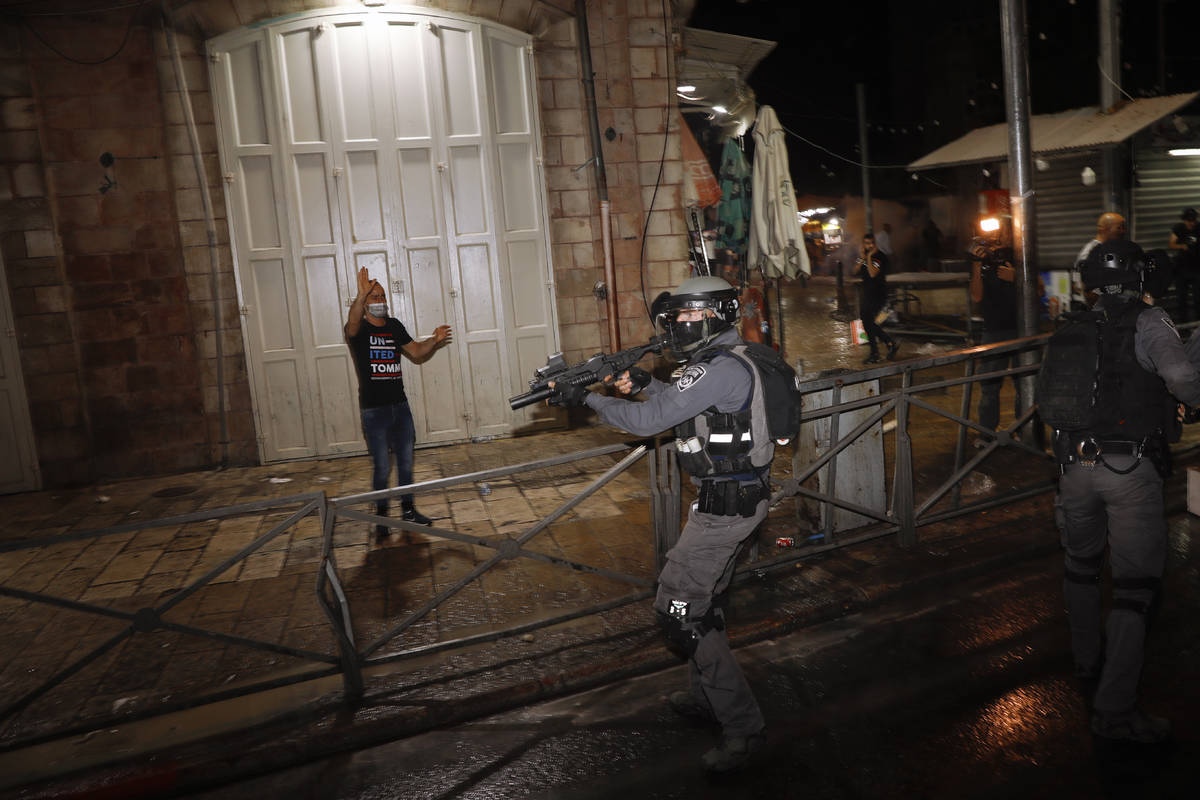 Israeli police officers aims his rifle during clashes with Palestinians near Damascus Gate just ...