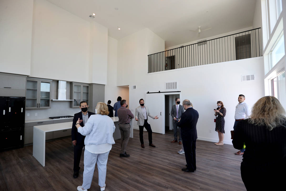 Patrick Brennan, development manager for Aspen Heights Partners, center, gives a tour of a pent ...