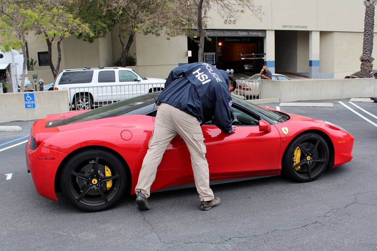 A special agent with HSI Los Angeles's El Camino Real Financial Crimes Task Force seizes a Ferr ...