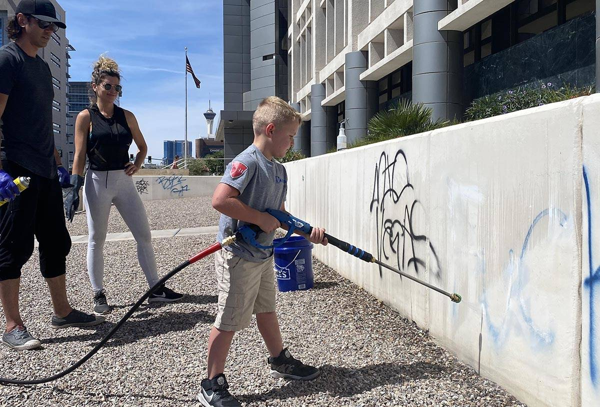 A group of volunteers on June 1, 2020, cleans up the defaced exterior of the Foley Federal buil ...