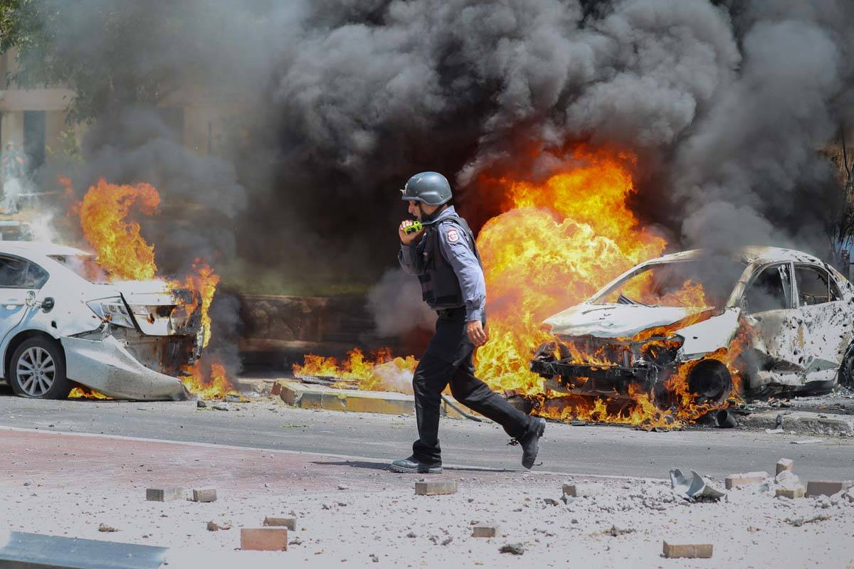 An Israeli firefighter walks next to cars hit by a missile fired from Gaza Strip, in the southe ...