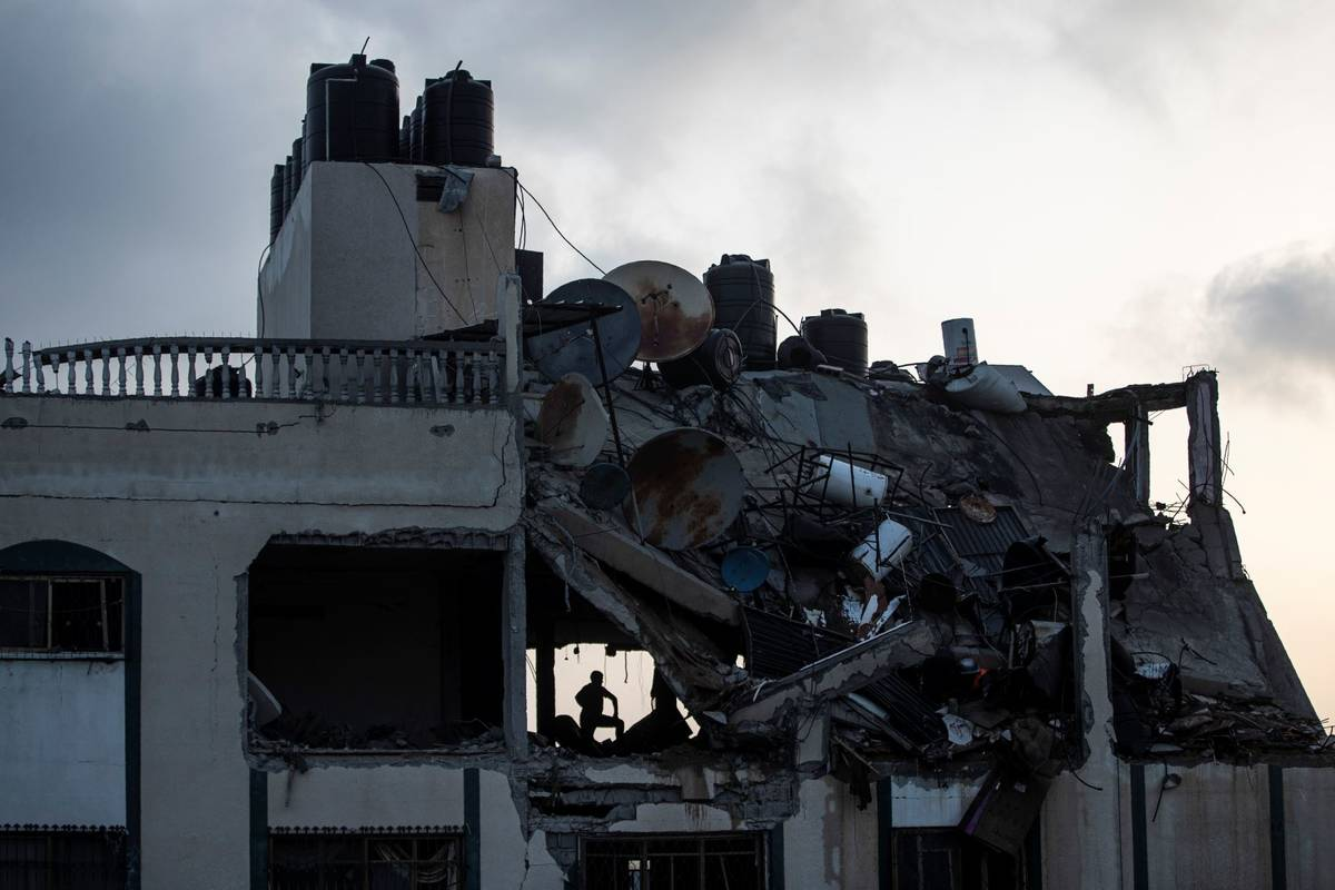A Palestinian searches for survivors under the rubble of a destroyed rooftop of a residential b ...