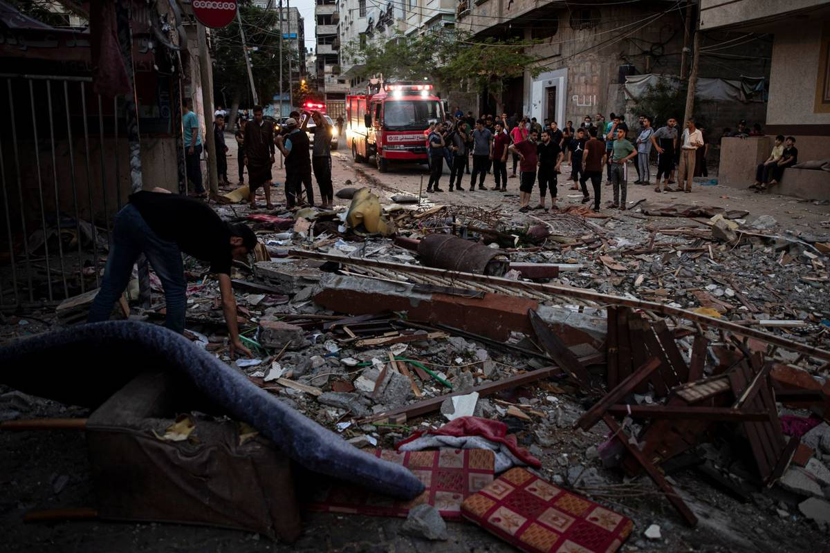 A Palestinian man inspects the rubble of a partially destroyed residential building after it wa ...