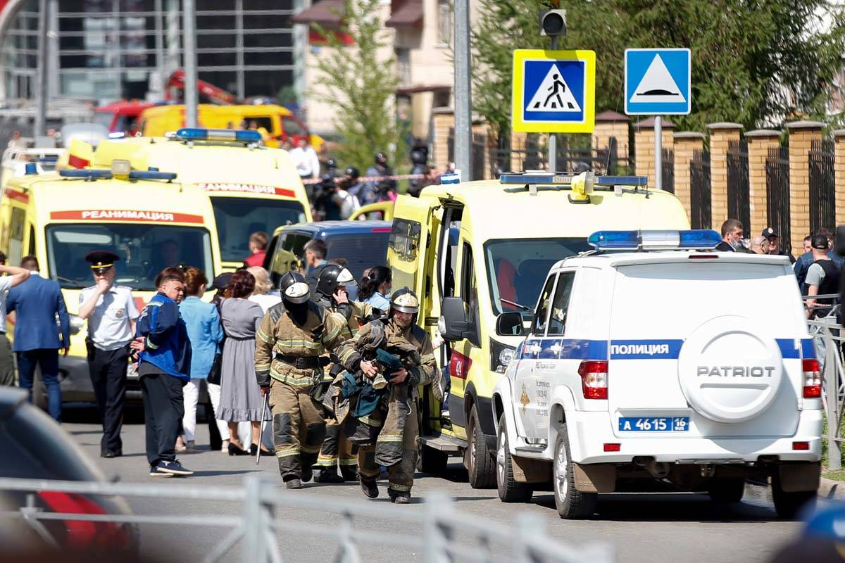 Firefighters walk past ambulances and police cars and a truck parked at a school after a shooti ...