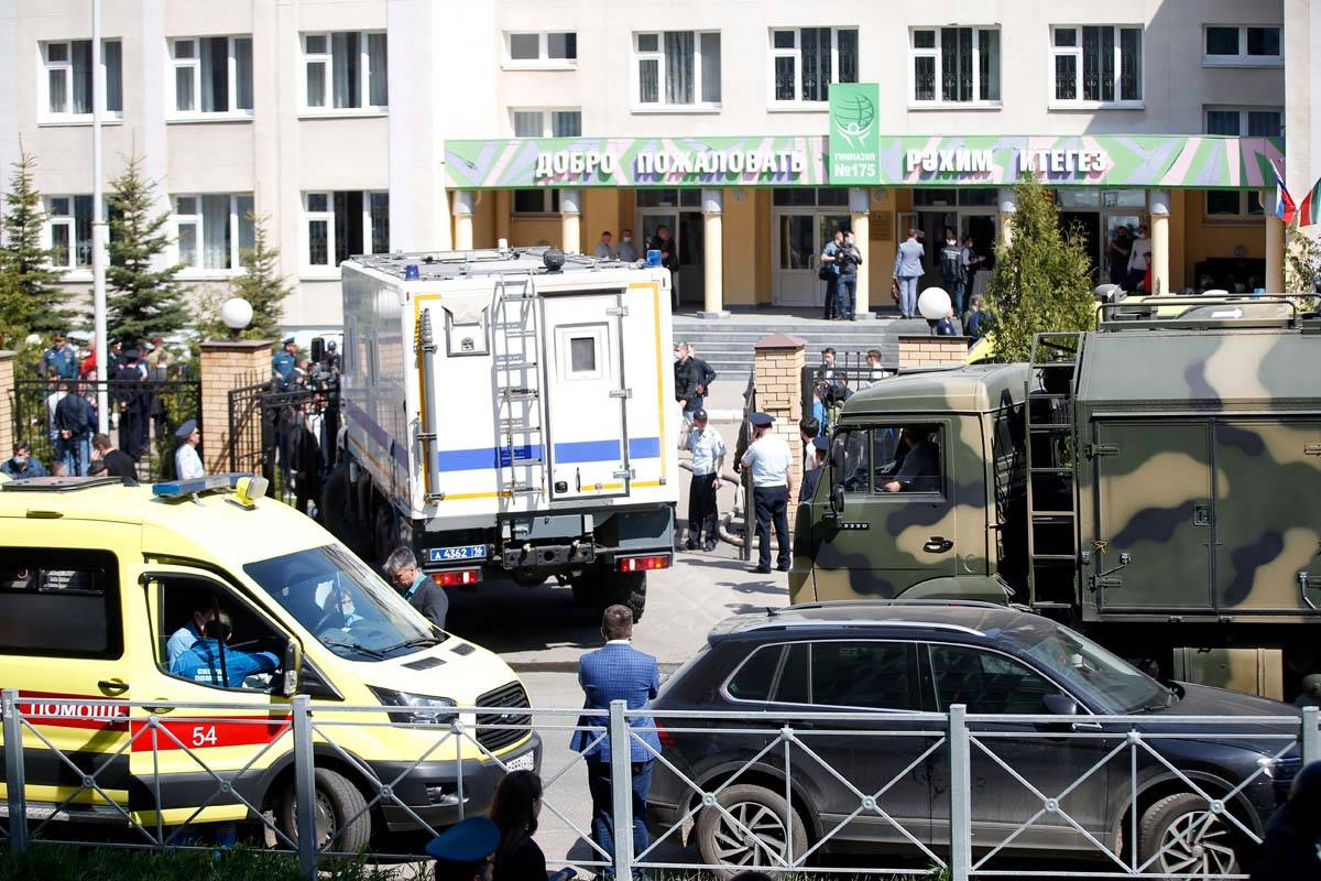 An ambulance and police trucks are parked at a school after a shooting in Kazan, Russia, Tuesda ...