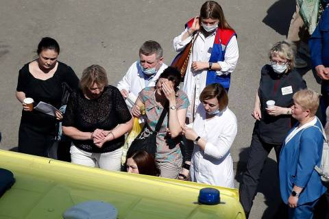 Medics and friends help a woman board an ambulance at a school after a shooting in Kazan, Russi ...