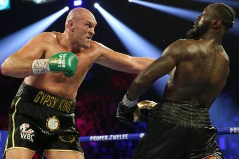Deontay Wilder, below, slips under Tyson Fury in round 4 of the WBC world heavyweight champions ...