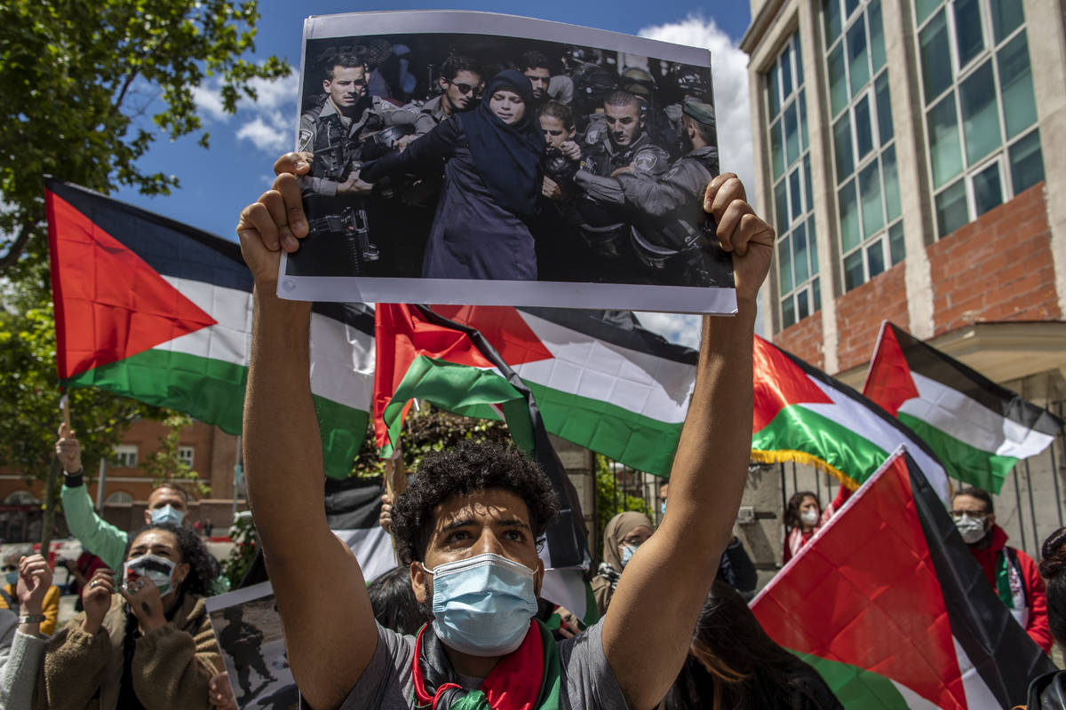 Protesters shout slogans and wave Palestinian flags in support of Palestinians during the lates ...