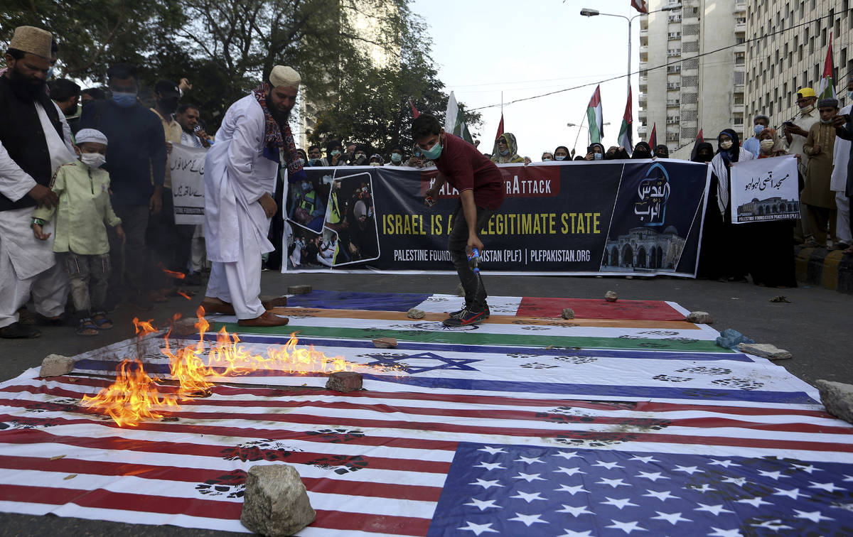 Members of a civil society group burn representations of Israeli, U.S. and Indian flags during ...