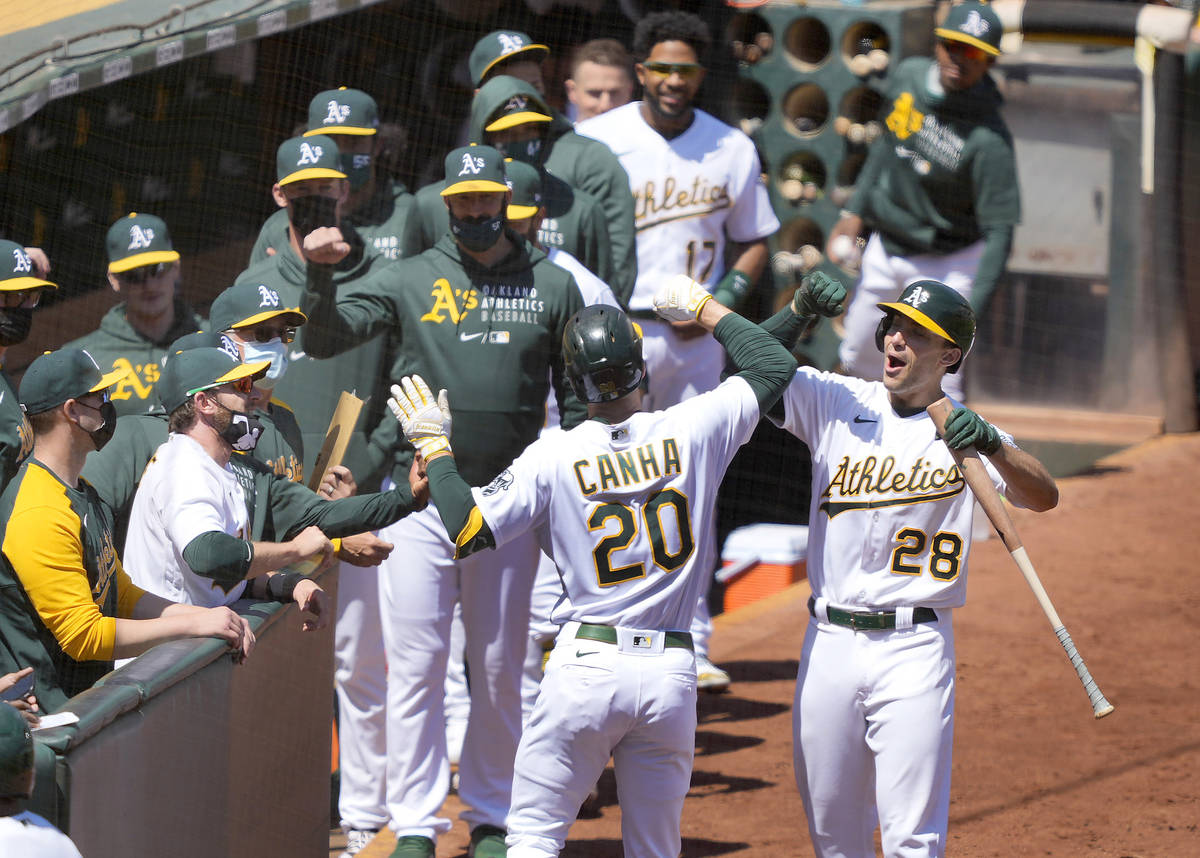 Oakland Athletics' Mark Canha (20) celebrates with Matt Olson (28) after hitting a solo home ru ...