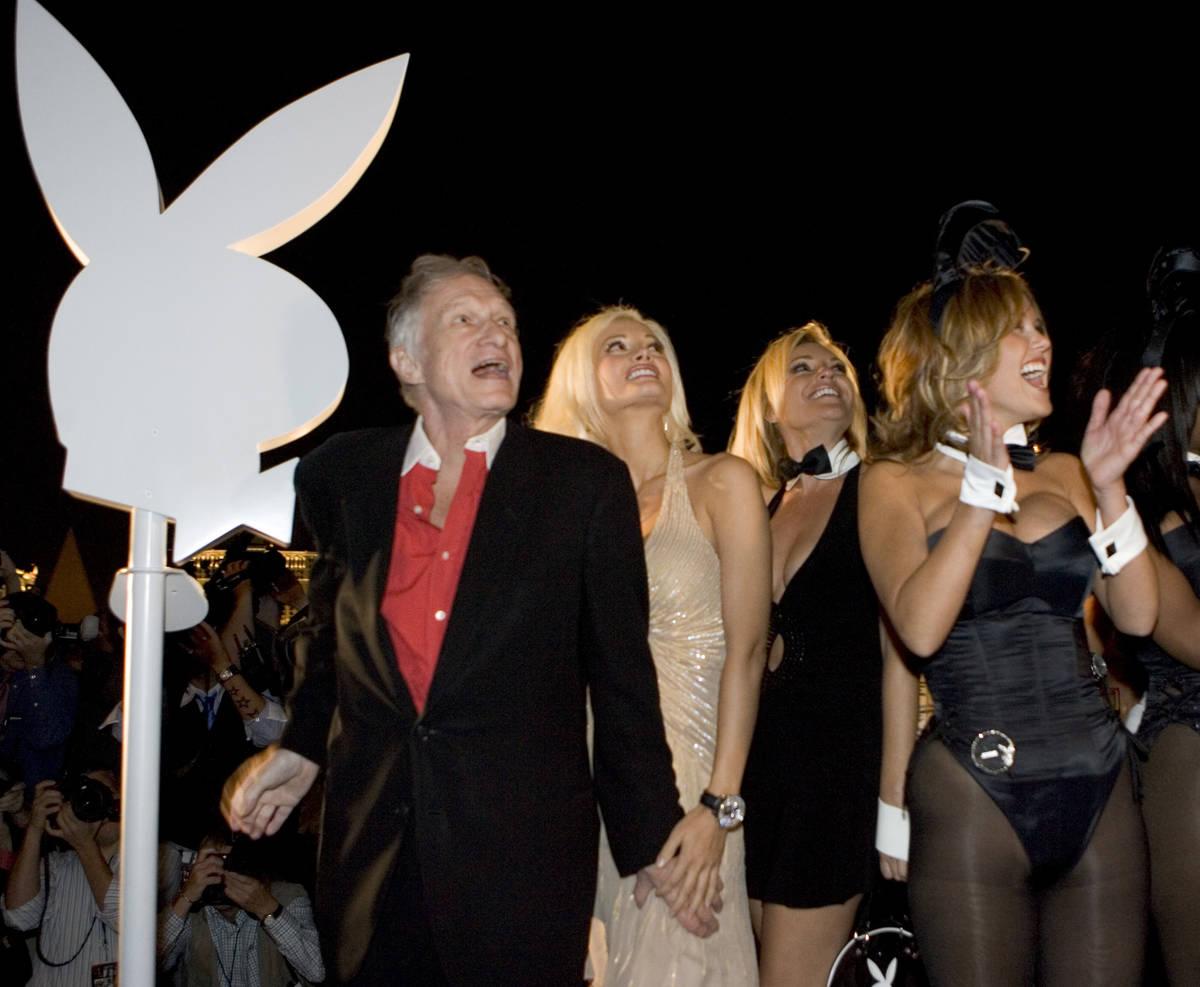 Playboy founder Hugh Hefner cheers the lighting of the Playboy logo at the opening of the Playb ...