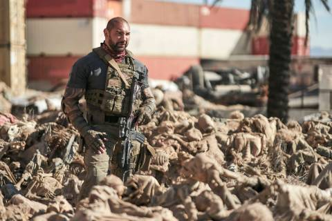 """Scott Ward (Dave Bautista) is up to his waist in skeletons in a scene from """"Army of the Dead."""" ..."""
