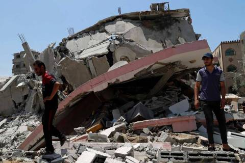 People walk amid the rubble of a destroyed residential building which was hit by Israeli airstr ...