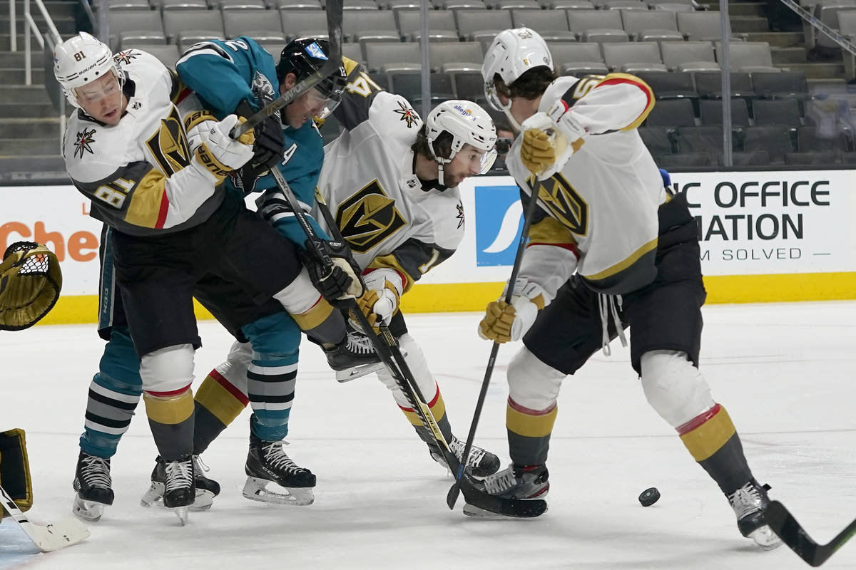 San Jose Sharks center Patrick Marleau, second from left, reaches for the puck between Vegas Go ...