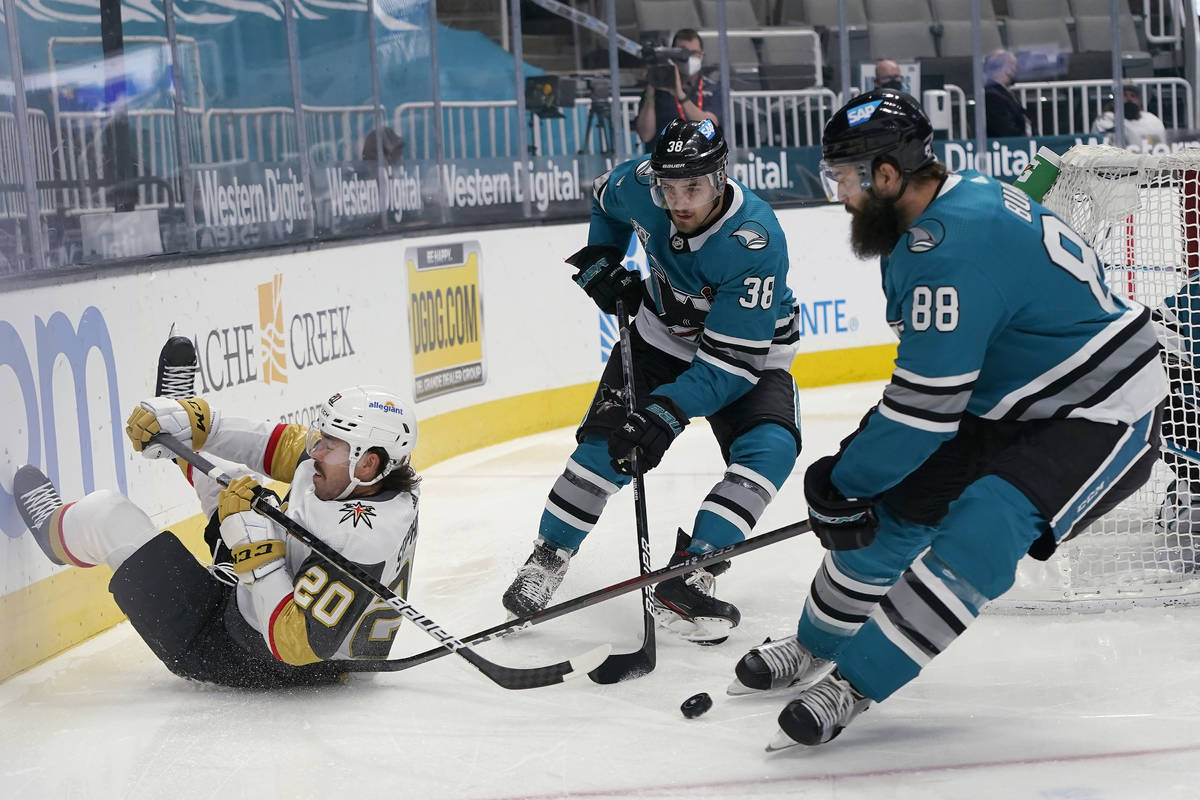 Vegas Golden Knights center Chandler Stephenson, left, reaches behind for the puck next to San ...