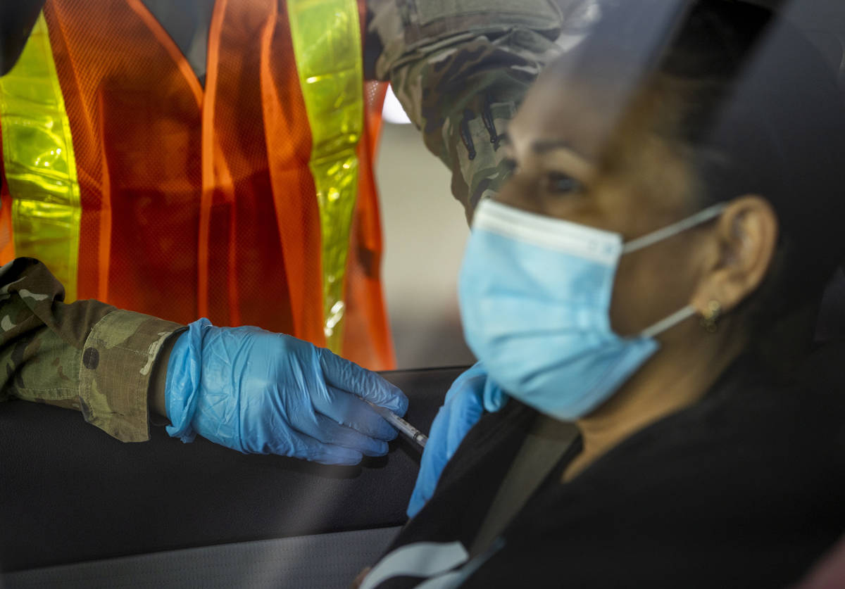 Nevada National Guard PFC Alicia Vavona gives an injection during a preview of the new drive-th ...