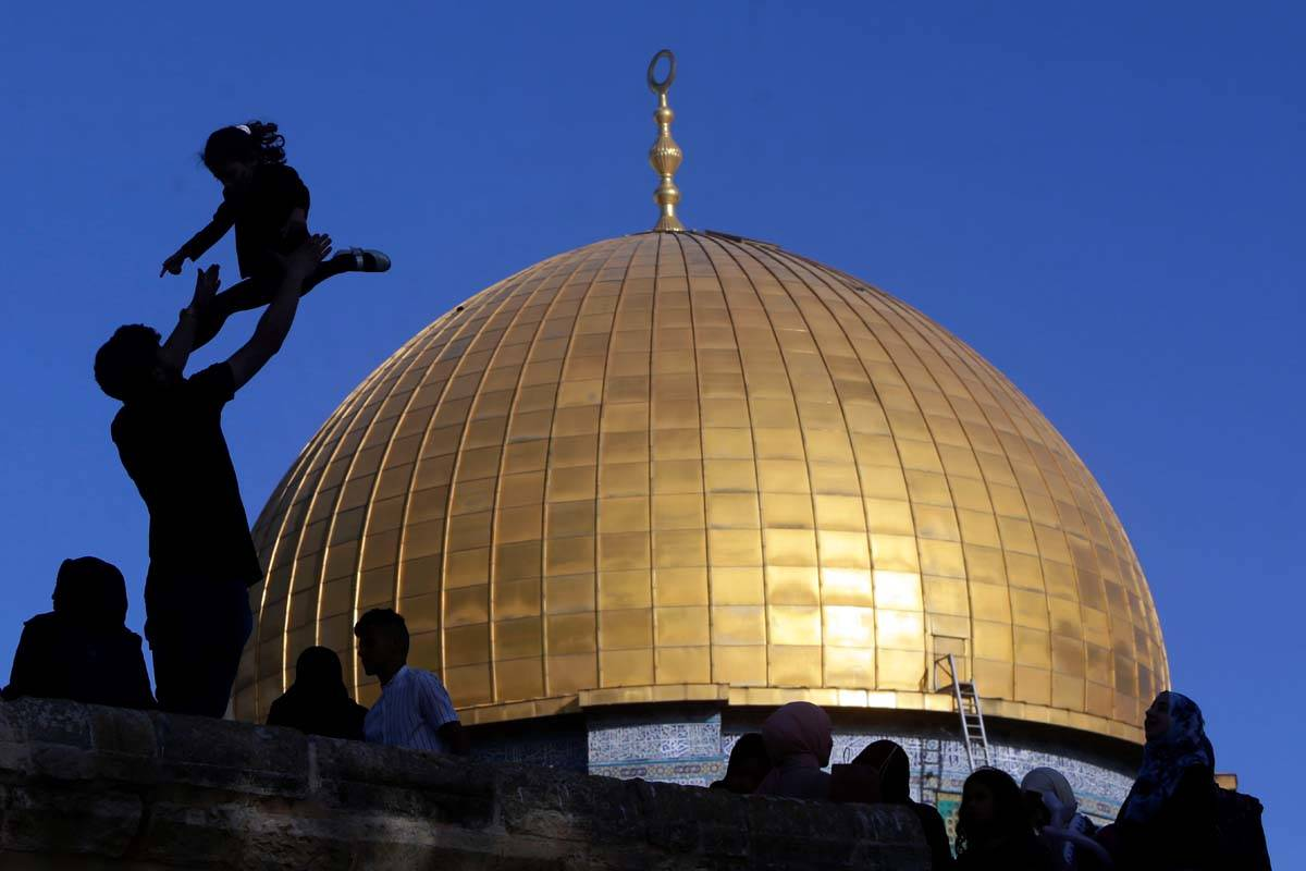 A girl is tossed into the air as people gather for Eid al-Fitr prayers at the Dome of the Rock ...