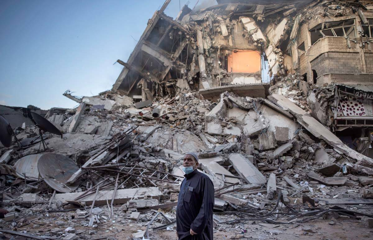 A Palestinian man looks at the destruction of a building hit by Israeli airstrikes in Gaza City ...