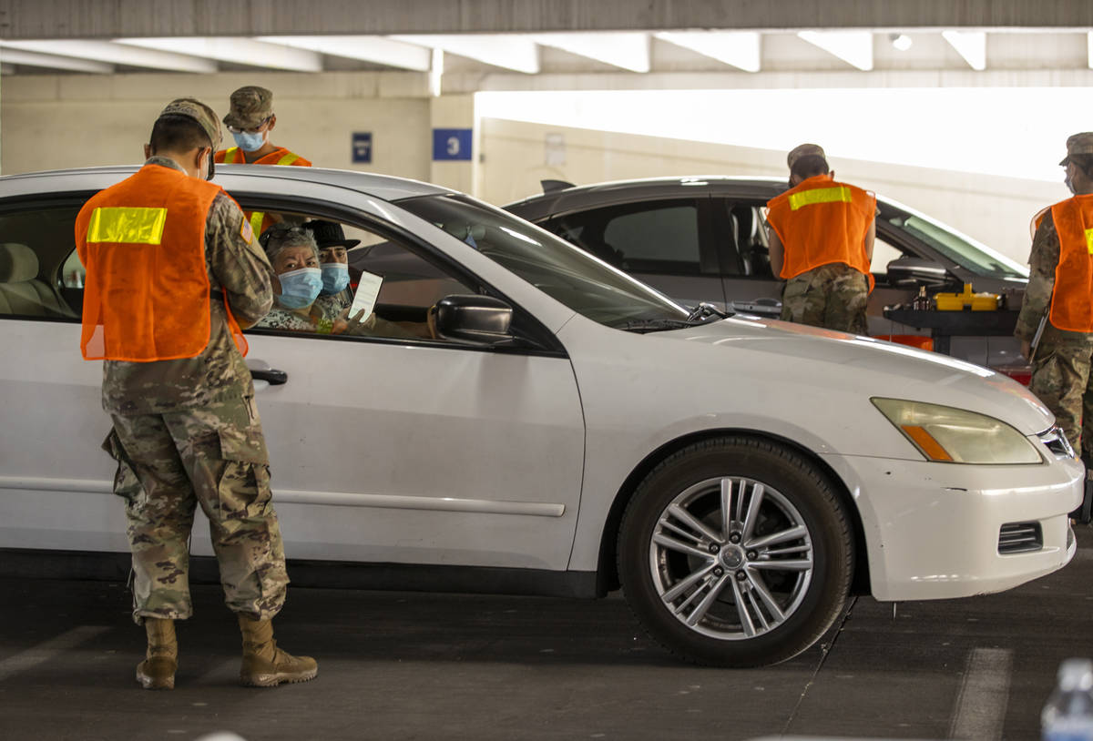 Nevada National Guardsmen begin to give injections during a preview of the new drive-through CO ...